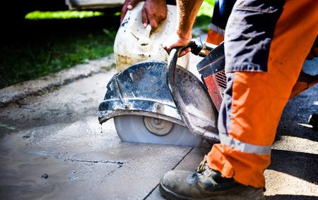 Construction worker cutting Asphalt paving stabs for sidewalk using a cut-off saw.