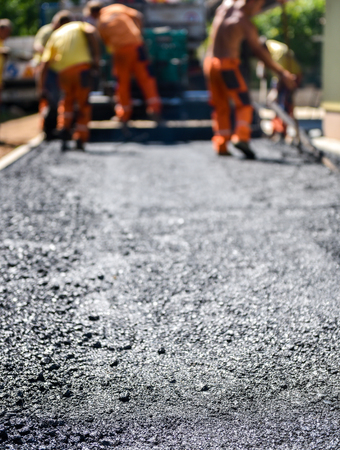 Team of Workers making and constructing asphalt road construction with finisher. The top layer of asphalt road on a private residence house driveway Stock Photo