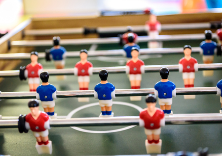 kicker: Close up of foosball Table Soccer Game match figures. Football Kicker Game with blue and red figurines.