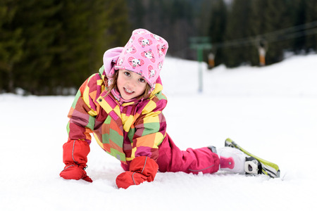 Little girl in winter outfit fell while skiing. Kid is lying in the snow with skis smiling. Happy ski experience in resort. Skiing accident.