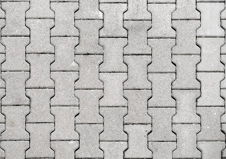 road paving: Concrete or cobble gray H Shaped pavement slabs or stones  for floor, wall or path. Traditional fence, court, backyard or road paving. Stock Photo