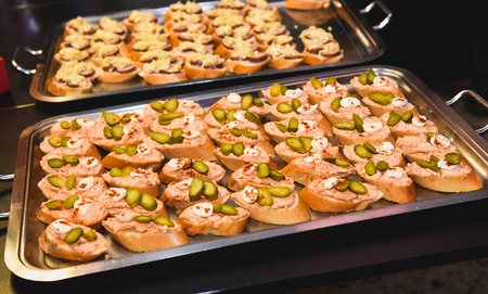 Home made canapes small sandwiches appetizers. Mix of different finger food snacks for a party or banquet on a plate. Stock Photo
