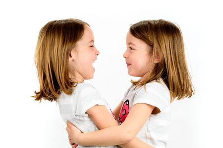 Twin girls are looking at each other and smiling. Concept of family and sisterly love. Profile side view of sisters playing.