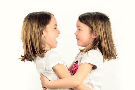 niñas gemelas: niñas gemelas están buscando el uno al otro y sonriendo. Concepto de familia y el amor fraternal. Perfil vista lateral de hermanas que juegan.