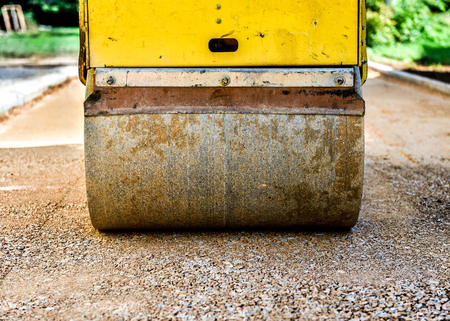 construction vibroroller: Construction roller or steamroller during road construction. Asphalt pavement works. Lower layer consists of construction gravel and is ready for upper asphalt layer. Stock Photo
