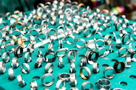 sample tray: Display with different designs of handmade silver rings on green stand. Close-up of handmade jewelry shop window display. Stock Photo