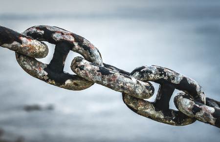 Old rusty anchor iron ship chain in sea port. Old fence made of obsolete boat chain elements with sea ocean in background.