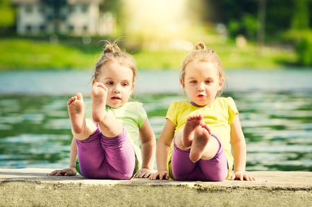 Twing girls are exercising on a lake shore