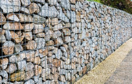 鉄線蛇籠岩の柵。金属製のケージは、岩でいっぱい。ケージにロック フェンスのテクスチャ背景。 写真素材 - 60684166
