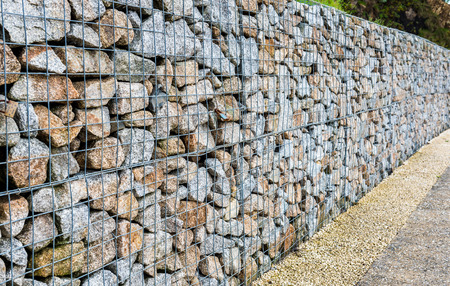 gabion mesh: Wire Gabion Rock Fence. Metal Cage filled with rocks. Texture background of rock fence with cage.
