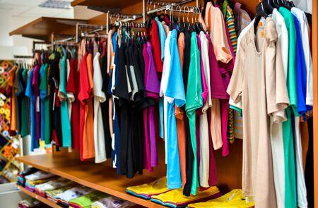 Diferente variedad de camisetas colgadas en almacenes de la fábrica. Vista de detalle de ropa y camisas en los hangares de plástico en una tienda. Foto de archivo - 61050851