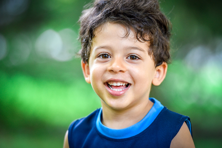 Happy mulatto boy child is smiling enjoying adopted life. Portrait of young boy in nature, park or outdoors. Concept of happy family or successful adoption or parenting.