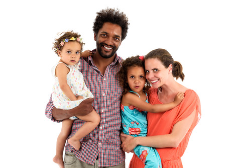 Happy interracial family is celebrating, laughing and having fun with Hispanic African American Father, Caucasian mother and Mulatto children daughters.  Isolated on white.