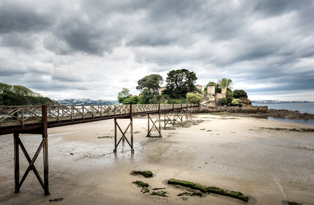 Landscape photo of old bridge in Santa Cruz island, Oleiros, Rias Altas, A Coruna, Spain in low tide. Stock Photo
