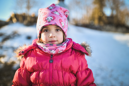 Little girl in winter clothes standing in mountain ski resort. A child with cap, scarf and winter jacket is looking at the camera outside in snowy nature. 免版税图像