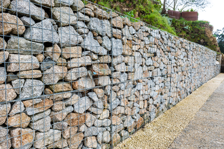 gabion: Wire Gabion Rock Fence. Metal Cage filled with rocks. Texture background of rock fence with cage.