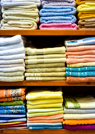 Different variety of colorful Towels piled in factory department store. Closeup view of multicolored bathing towels in a shop. Shopping display with shelfs. Stock Photo