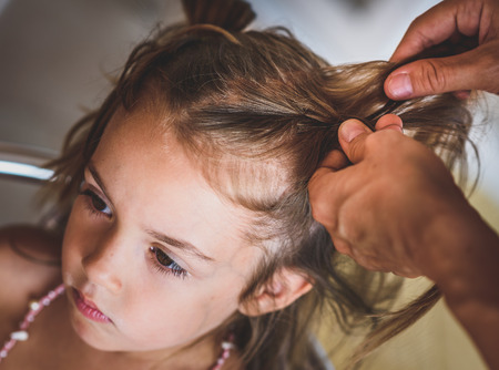 braiding: Mother is making of braids on little daughters head. Hairdresser is braiding the hair on a young girl. Getting ready for school.
