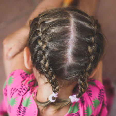 Braids on little girls head. Young woman with braided hair is sitting in the pink dress with hair made into two french braids. Stock Photo
