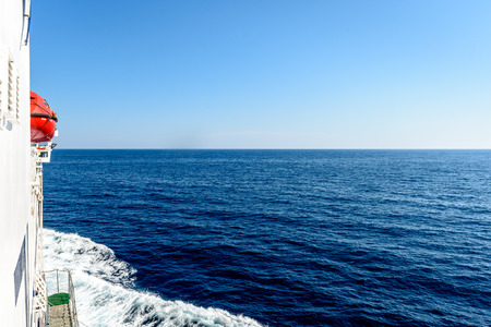 starboard: Starboard side of a ferry boat on the Adriatic Sea. The wake from a giant ship cruising through the blue ocean and clear skies.