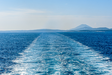 churning: Wake water trail from a ferry ship in Croatia. Boat is leaving churning sea and waves behind. Blue ocean and skies on a sunny day.