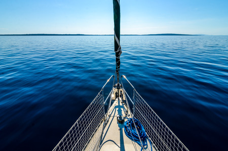 bow of boat: Front view of sailing boat on the sea. Bow side of yacht or sail boat gliding through calm sea in Adriatic sea on the sunny day.