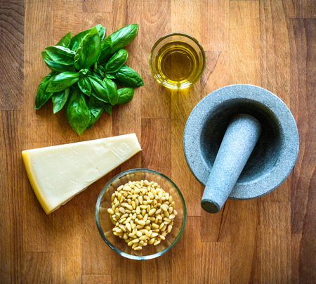 Making of homemade pesto Genovese with all ingredients. Basil, olive oil, Parmesan cheese and grinder on a wooden desk. Everythe ingredient for making delicious pasta sauce.