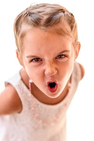 Retrato de una niña con trenzas gritando. Niño con el pelo trenzado está mirando a la cámara, gritando.