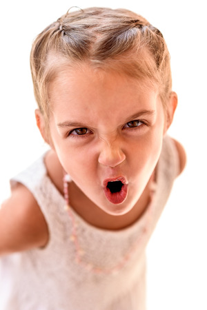 Portrait of a little girl with braids screaming. Child with braided hair is looking at the camera, yelling.