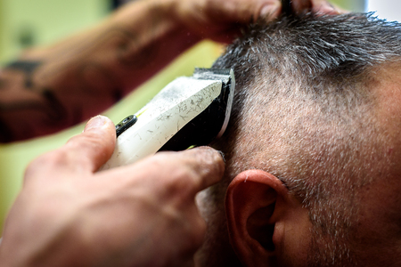 Close-up of a man getting his hair shaved with trimmer. Hairdressers hand is holding electric trimmer and shaving a costumers head. Stock Photo