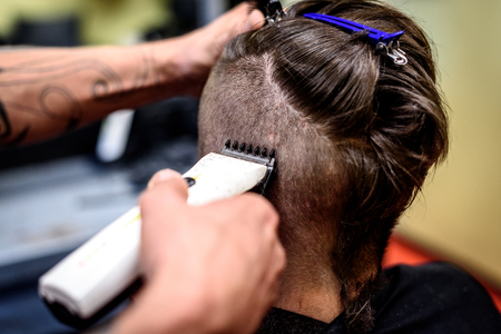 COSTUMERS: Close-up of a man getting his hair shaved with trimmer. Hairdressers hand is holding electric trimmer and shaving a costumers head. Stock Photo