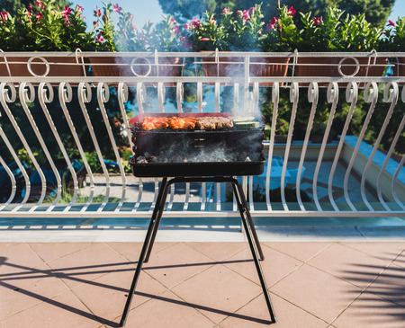 Delicious meat on barbecue grill with coal on balcony. Grilling food on a balcony or a terrace with wonderful view. Small cheap BBQ grill at home. Standard-Bild