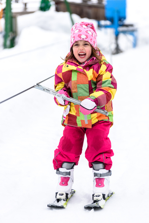 kids at the ski lift: Little girl is learning to ski in ski resort. Child is using ski baby lift conveyor skiing for the first time. Active children are happy. Stock Photo