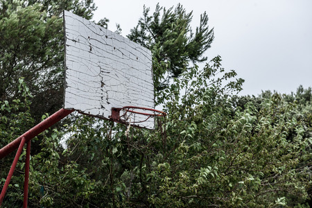 different goals: Old abandoned school sports court or schoolyard for different activities. Ruins of a sport venue abandoned long time ago with soccer, handball or football goals, basketball hoops and boards and destroyed concrete plates.