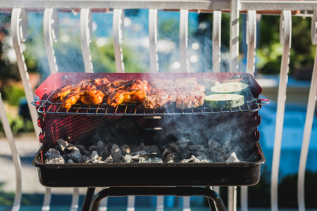 Delicious meat on barbecue grill with coal on balcony. Grilling food on a balcony or a terrace with wonderful view. Small cheap BBQ grill at home.