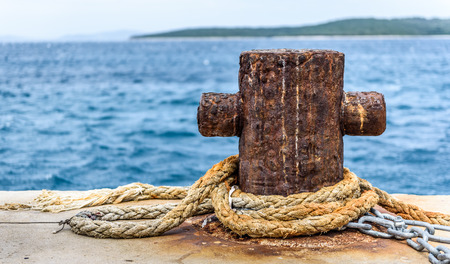 Old rusty steel mooring bollard pole on a pier. The best way for boat or ship mooring in harbor. Croatia, Silba.