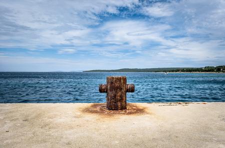 mooring bollard: Old rusty steel mooring bollard pole on a pier. The best way for boat or ship mooring in harbor. Croatia, Silba.