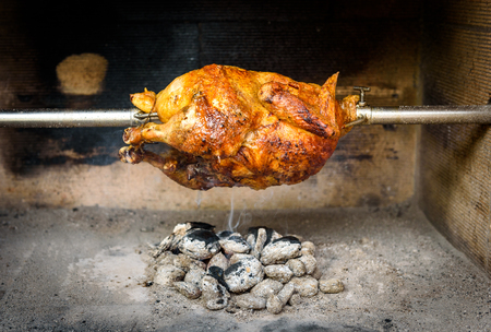 briquettes: Cooking and preparing rotisserie chicken on the grill with Charcoal and Briquettes in the professional steak house or barbecue restaurant