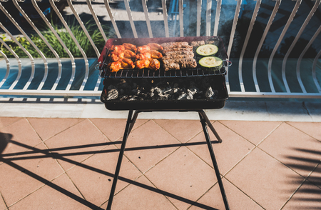 Delicious meat on barbecue grill with coal on balcony. Grilling food on a balcony or a terrace with wonderful view. Small cheap BBQ grill at home. Imagens