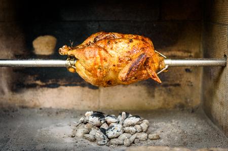 pollo rostizado: Cocinar y preparar el pollo asado a la parrilla con carbón vegetal y briquetas en el asador o parrilla profesional restaurante