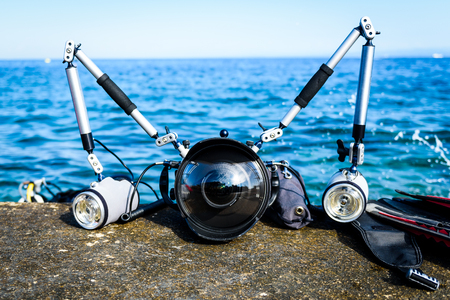 Professional underwater photography equipment for DSLR camera with strobes. Wide angle dome for fish-eye dual flashes with arms in aluminium casing on a pier with blue sea in the background.