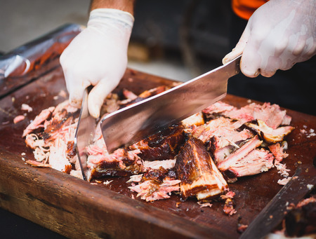Chef Hands cutting Grilled spare beef or pork back ribs prepared in smoker with a hatchet. Delicious roasted cuts of meet made on barbecue smoker on a wooden cutting desk. Imagens