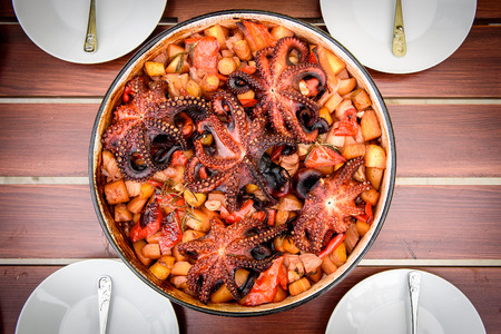 Preparing and Cooking of octopus in traditional Balkan Croatian Greek Mediterranean meal Peka in metal pots called sac sach or sache or a lid. Dish is ready on a wooden table. Traditional roast of octopus with potatoes onions garlic carrots and spices.