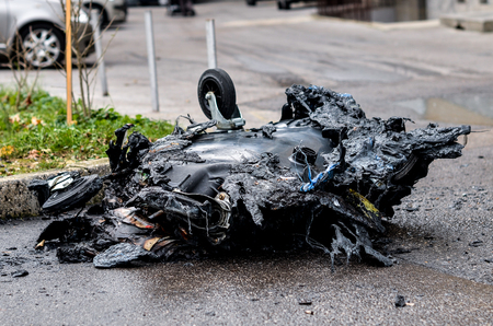 Burnt and melted trash can form a fire. Burned trash in waste container in the city is melted due to hot fire inside. Stock Photo
