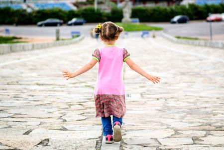 empedrado: La niña se está ejecutando en piedra paseo pavimentado a la Torre de Hércules, A Coruña - España. Concepto de la libertad, la infancia y el patrimonio nacional.