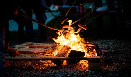 上のホットドッグのソーセージを調理し、キャンプの火を開きます。木造支店 - で焚き火の炎、夜自然にスティック槍以上グリルの食品。食品を準備する方法をスカウトします。