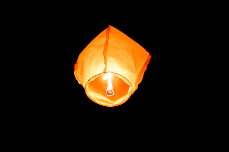 Orange paper sky flaming lantern, flying lantern, floating lantern, hot-air balloon is flying with a candle flame in the night. Popular Celebration or Holiday event. Imagens