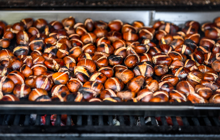 roasting pan: Roasting grilled Chestnuts on barbecue with flames, fire and charcoal. Homemade roasted chestnuts are prepared in BBQ grill fireplace.