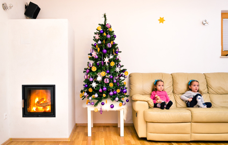niñas gemelas: Children and Christmas tree in modern luxury apartment with fireplace. Twin girls are sitting on a sofa next to home decorated Christmas tree with hot fire and flames burning in the fireplace.