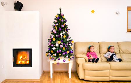 niñas gemelas: Los niños y el árbol de Navidad en el apartamento moderno de lujo con chimenea. niñas gemelas están sentados en un sofá junto a la casa del árbol de Navidad decorado con fuego y llamas que ardían en la chimenea.